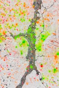 Taches de peinture verte et orange sur la route goudronnée