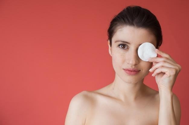 Taches de rousseur femme caucasienne se couvre les yeux avec un disque de coton souriant sur un mur rouge avec des épaules nues