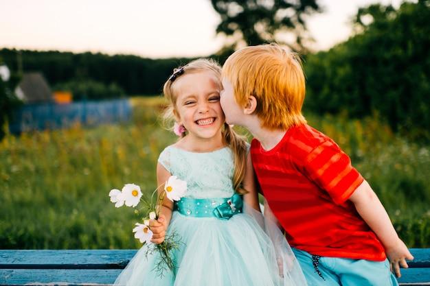 Taches de son garçon kising peu timide belle fille en robe de vacances bleue en plein air sur route dans la campagne au coucher du soleil dans la nature