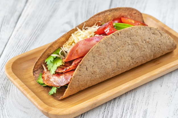 Taco au jambon et légumes sur la plaque en bois de service