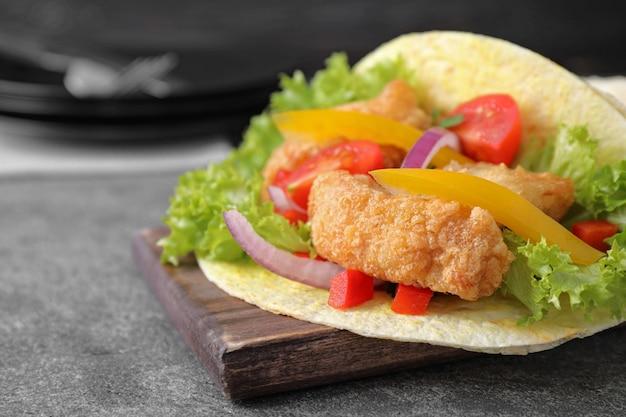 Taco au poisson délicieux servi sur table grise, gros plan