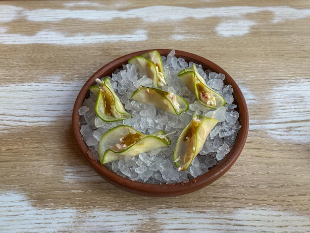 Taco de crabe avec sauce à la mangue épicée sur un coussin de glace dans une assiette en céramique sur une table en bois. vue de dessus