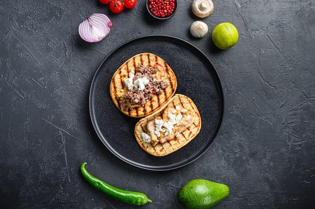 Taco mexicain traditionnel avec du poulet et du boeuf avec des ingrédients un côté sur une plaque noire sur fond texturé noir vue de dessus.