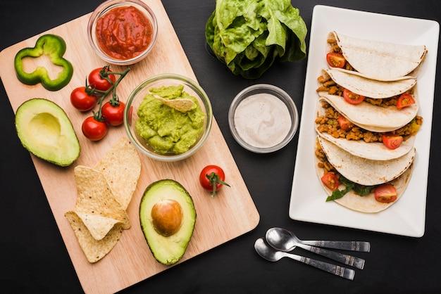Tacos sur assiette près de planche à découper avec des légumes et des sauces
