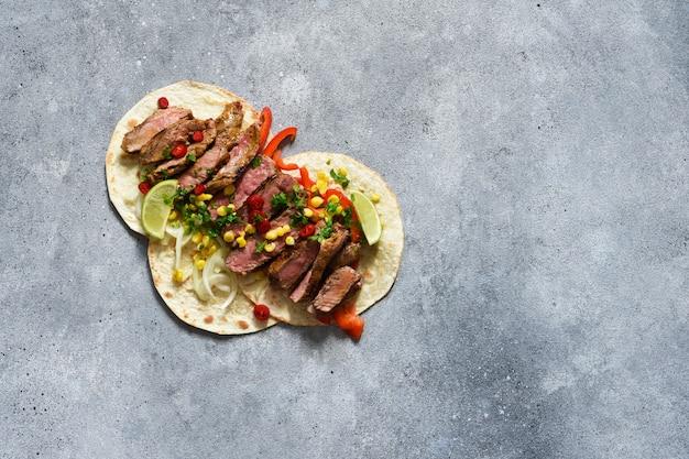 Tacos au bœuf, poivre et maïs avec sauce sur fond de béton. cuisine mexicaine traditionnelle.