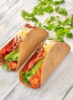 Tacos au jambon et légumes sur l'assiette en bois de service