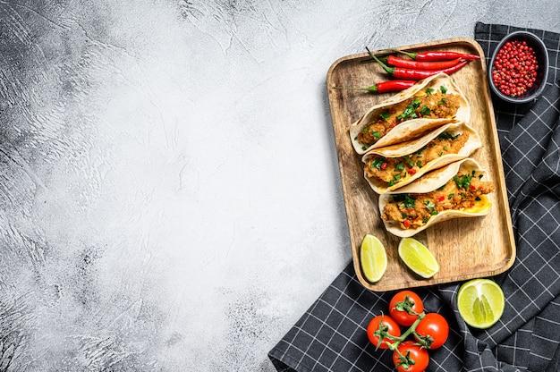 Tacos au poulet croustillant, persil, fromage et piments. fond blanc. vue de dessus. espace copie