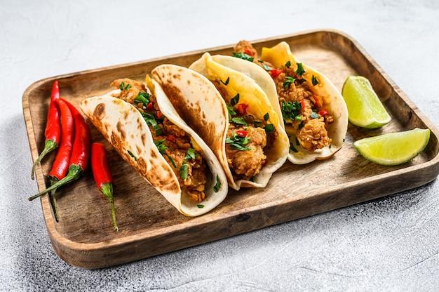 Tacos au poulet croustillant, persil, fromage et piments. fond blanc. vue de dessus
