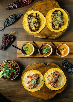 Tacos au poulet grillé et au foie gras servis sur une planche à découper en bois avec différentes sauces.