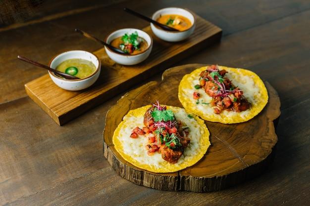 Tacos au poulet grillé avec salade de tomates sur une planche à découper en bois avec des sauces