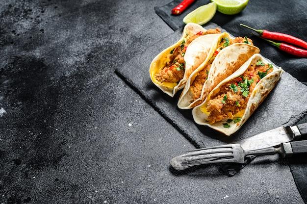 Tacos carnitas mexicains au persil, fromage et piment. fond noir.