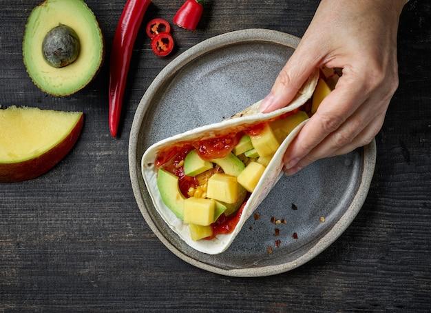 Tacos de cuisine mexicaine à la main de l'homme sur une table en bois foncé, vue de dessus