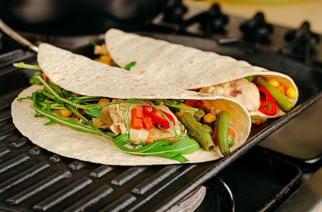 Tacos épicés mexicains faits maison avec du poulet et des légumes sur la lèchefrite.