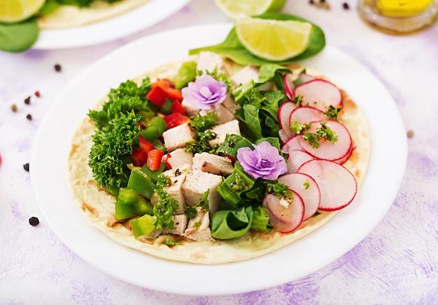 Tacos de maïs mexicains sains avec poitrine de poulet bouillie, épinards, radis et paprika.
