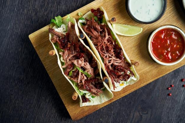 Tacos mexicains appétissants avec du bœuf, du chou, des oignons et du persil dans des stands spéciaux. cuisine mexicaine traditionnelle