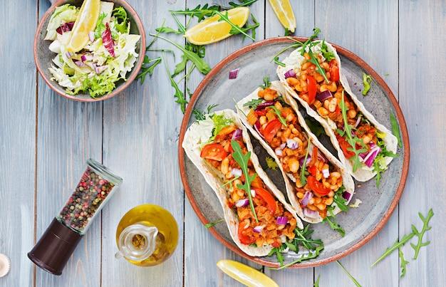 Tacos mexicains au bœuf, haricots à la sauce tomate et salsa. mise à plat. vue de dessus.