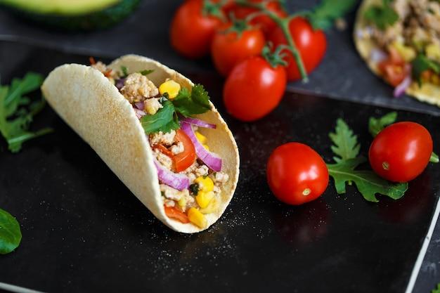 Tacos mexicains au porc, légumes et épices sur une assiette en pierre noire sur un fond sombre avec des ingrédients pour les tacos