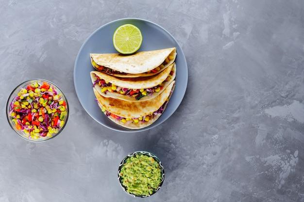 Tacos mexicains aux légumes et guacamole sur fond gris. tacos végétaliens au maïs, chou violet et tomates sur une assiette grise. espace de copie. vue de dessus
