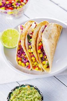 Tacos mexicains avec différents légumes et guacamole sur des tableaux blancs. tacos végétaliens au maïs, chou violet et tomates sur une assiette blanche. cuisine mexicaine