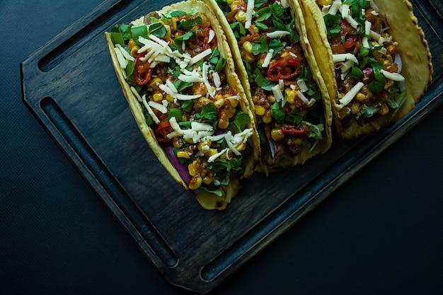 Tacos mexicains avec viande, fromage, maïs, oignons et herbes de porc sur une planche de bois