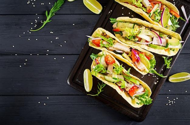 Tacos mexicains à la viande de poulet, avocat, tomate, concombre et oignon rouge. tortilla saine. enveloppez les aliments. taco. vue de dessus