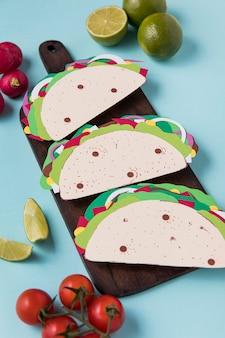 Tacos en papier à angle élevé sur planche de bois