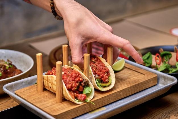 Tacos de porc mexicain traditionnel de rue avec boeuf, tomates, avocat, piment et oignons dans une tortilla de maïs jaune appelée al pastor