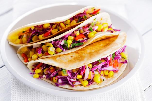 Tacos végétaliens au maïs, chou violet et tomates sur une assiette blanche. tacos mexicains avec différents légumes sur des tableaux blancs. nourriture saine. cuisine mexicaine