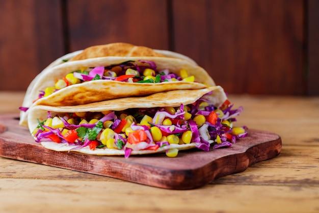 Tacos végétaliens avec divers légumes sur une planche à découper. tacos au maïs sucré, chou violet et tomates sur planches de bois. espace de copie