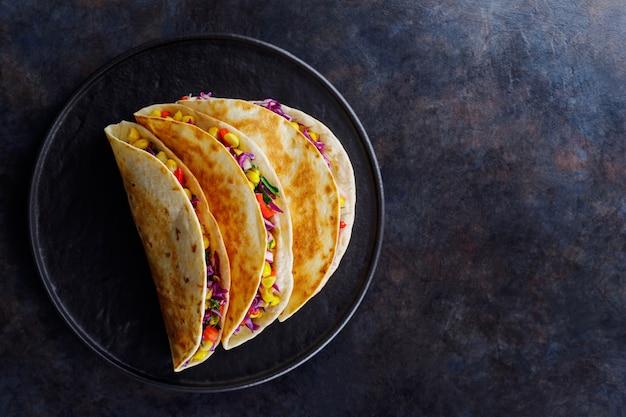 Tacos végétariens au maïs sucré, chou violet et tomates sur une plaque noire. tacos aux légumes et sauce guacamole sur fond sombre. espace de copie. vue de dessus