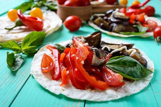 Tacos végétariens aux aubergines, tomates cerises, poivrons doux sur table en bois clair