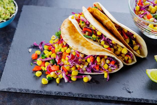 Tacos végétariens avec divers légumes, guacamole et citron vert en tranches sur fond sombre. tacos au maïs sucré, chou violet et poivre sur une ardoise. espace de copie