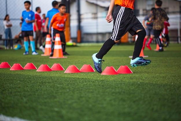 Tactiques de ballon de football sur terrain en herbe avec cône de barrière pour entraîner les enfants à sauter dans l'académie de football