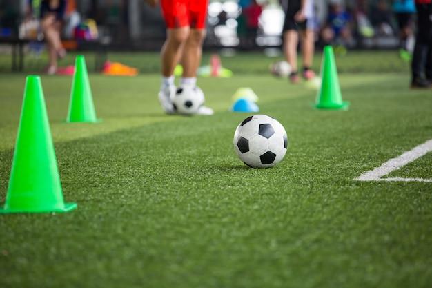 Tactiques de ballon de football sur terrain en herbe avec cône pour fond de formation formation des enfants à l'académie de football