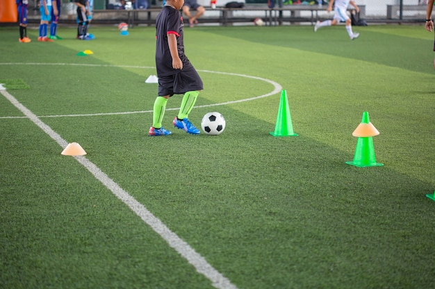 Tactiques de ballon de football sur terrain en herbe avec cône pour la formation de la thaïlande en arrière-plan formation des enfants à l'académie de football