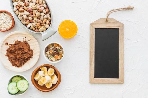 Tag d'ardoise en bois avec des ingrédients sur fond blanc