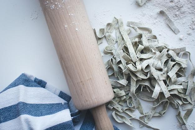 Tagliatelle de pâtes recouverte de farine avec un rouleau en bois sur fond blanc