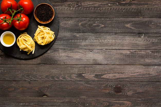 Tagliatelle à la tomate et au basilic, faite à la maison, sur une surface en bois.