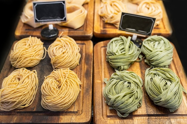 Tagliatelles aux épinards et tarte aux légumes grillés sur des plateaux en bois dans le magasin. pâtes crues italiennes. délicieux plat traditionnel semi-fini en cuisine, avec des étiquettes de prix vides