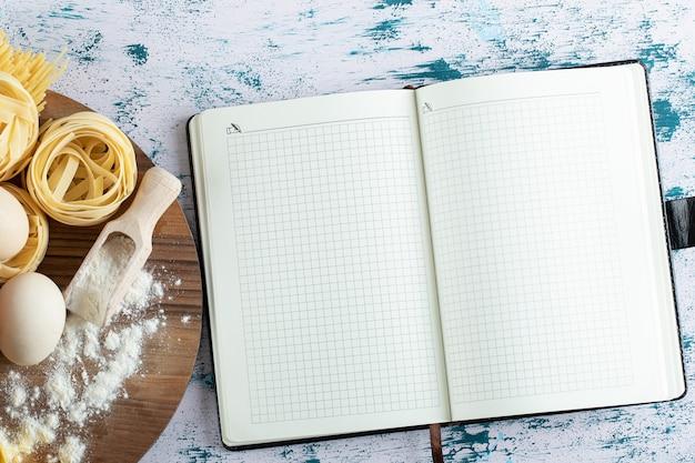 Tagliatelles aux oeufs et farine sur planche de bois et cahier.