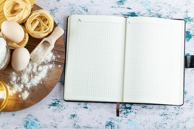 Tagliatelles à l'huile, oeuf et bol de farine sur planche de bois et cahier.