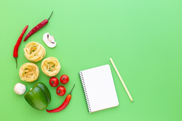 Tagliatelles pâtes crues nids et légumes sur fond vert vue de dessus copie espace recette de cuisson