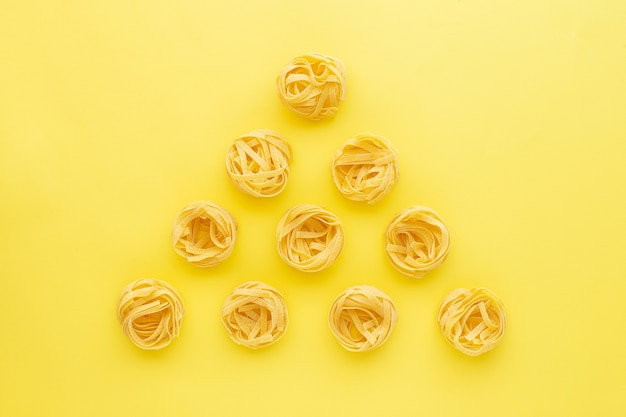 Tagliatelles pâtes crues nids pyramide sur fond jaune vue de dessus