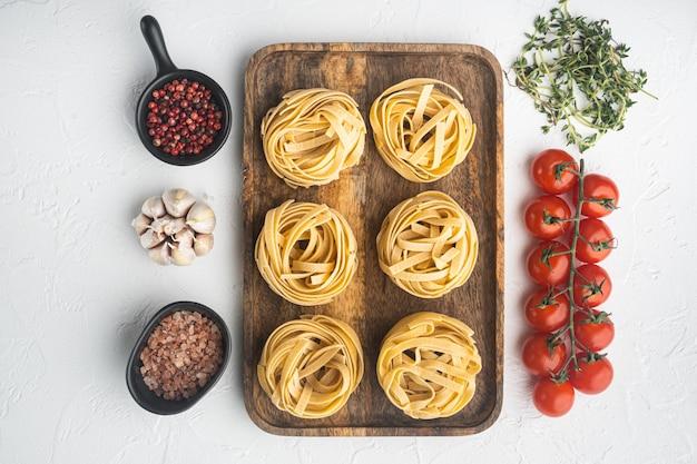 Tagliatelles de pâtes crues avec des tomates fraîches et des herbes, sur table en pierre blanche, vue de dessus à plat