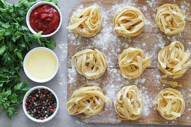 Tagliatelles de pâtes italiennes crues sur planche de bois avec des sauces et des herbes sur fond gris