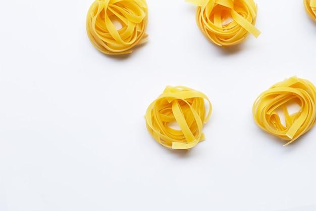 Tagliatelles de pâtes italiennes non cuites sur fond blanc