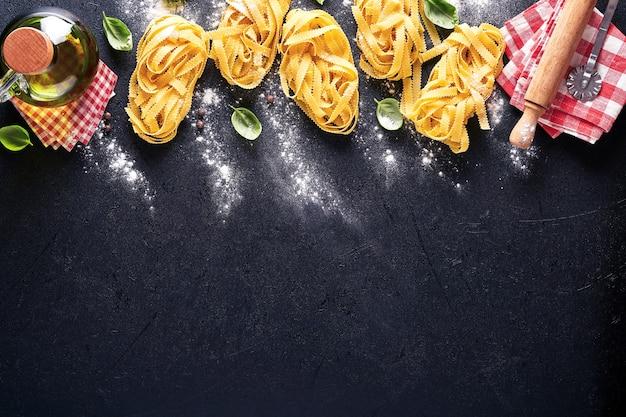 Tagliatelles. pâtes maison, feuilles de basilic, farine, poivre, huile d'olive et tomate cerise sur fond noir foncé. notion de nourriture. maquette. horizontal avec espace de copie.
