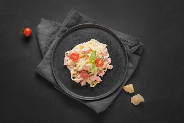 Tagliatelles de pâtes à la truite et crème sur fond noir. délicieux déjeuner méditerranéen.