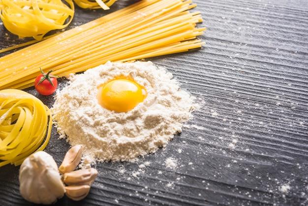 Tagliatelles et spaghettis avec ingrédients sur fond de planches de bois