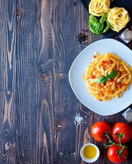 Tagliatelles à la tomate et au basilic faites à la maison sur un fond en bois.